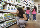 Mother with young daughters in grocery store — Stock Photo