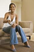 африканская женщина, сидя на диване, с помощью пульта дистанционного управления — Стоковое фото