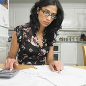 Hispanic woman at kitchen table paying bills — Stock Photo