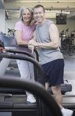 Pár stojící na běžeckém pásu v tělocvičně — Stock fotografie