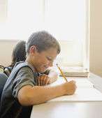 Jeune garçon travaillant au bureau en salle de classe — Photo