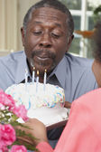 Senior African American man blowing out birthday candles — Stock Photo