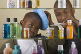 African father taking son's temperature in front of medicine cabinet — Stock Photo