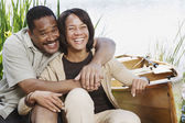 Middle-aged African couple laughing next to canoe — Stock Photo