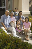 Multi-generational Asian family smiling on front steps of house — Stock Photo