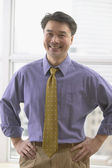 Asian businessman smiling with hands on hips — Stock Photo