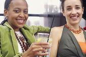Two women sitting on sofa smiling — Stock Photo