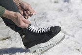 Close up of man lacing ice skate — Stock Photo