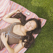 High angle view of Asian woman laying on blanket in grass — Stock Photo