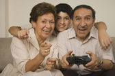 Hispanic grandparents playing video games with grandson — Stock Photo