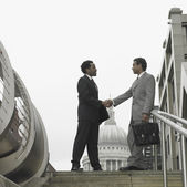 Two businessmen shaking hands in urban area — Stock Photo