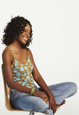 Studio shot of African woman in chair — Stock Photo