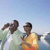 Altes afrikanischen paar nehmen foto neben wasser — Stockfoto