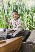 Jovem rapaz africano na doca com vara de pesca — Foto Stock