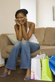 African woman smiling on sofa next to shopping bags — Stock Photo