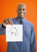 African man holding up napkin with house drawn on it — Stock Photo
