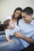 Coppia africana, giocando con il bambino sul divano — Foto Stock