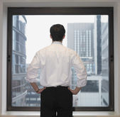 Rear view of businessman looking out window — Stock Photo