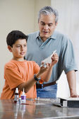 Hispanic father and son building model airplane — Stock Photo