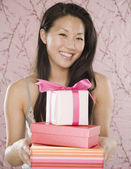 Young Asian woman smiling with stack of gifts — Stock Photo