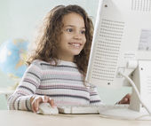 Young girl using computer in classroom — Stock Photo