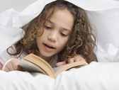 Young girl reading under sheets — Stock Photo