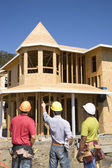 Male construction workers pointing at house under construction — Stock Photo