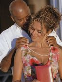 African American man putting necklace on African American woman — Stok fotoğraf