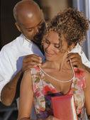 Afryki amerykański człowiek wprowadzenie naszyjnik na african american kobieta — Zdjęcie stockowe