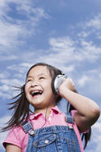Young Asian girl holding listening to music outdoors — Stock Photo