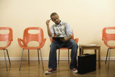 African man filling out form in waiting area — Stock Photo