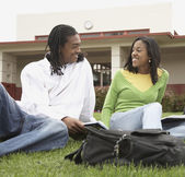 Young African couple studying in grass — Stock Photo