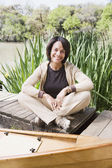 Middle-aged African woman sitting on dock smiling — Stock Photo