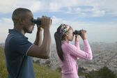 African couple using binoculars above city — Stock Photo