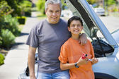 Hispanic father and son standing in front of car with hood up — Stock Photo
