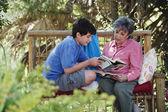 İspanyol büyükanne ve torunu açık havada okuma — Stok fotoğraf
