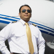 Asian male pilot standing near airplane — Stock Photo #23272944