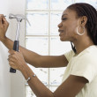 African woman hammering nail into wall — Stock Photo
