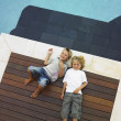 Two brothers laying next to swimming pool — Stock Photo