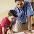Indian father helping son with homework — Stock Photo
