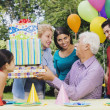 Senior Hispanic man receiving gifts at birthday party — Stock Photo