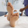 Close up of African boy's bare feet in hospital bed — Stock Photo