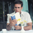Hispanic man reading book at outdoor cafe — Stock Photo