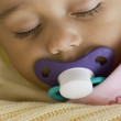 Close up of Hispanic baby sleeping with pacifier - Stock Photo