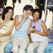 Hispanic women sitting on edge of fountain talking cell phones — Stock Photo