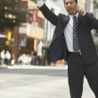 Asian businessman hailing taxicab in urban area — Stock Photo