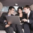 Three Hispanic businesspeople looking at laptop in limousine — Stock Photo