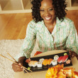 African woman eating sushi at home — Stock Photo