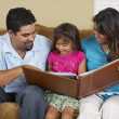 Hispanic family looking at photo album — Stock Photo