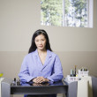 Asian nail technician sitting at station - Stock Photo